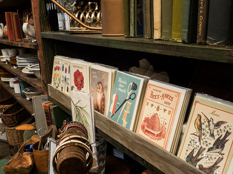 A selection of vintage cards, antique books, and tableware